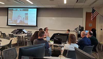 Photo of in-person and online participants collaborating